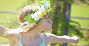 Child wearing a wreath on her head, dancing outside