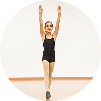 Young girl wearing black leotard and jazz shoes raising her hands high