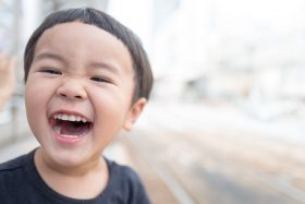 A young boy smiles broadly. Photo by kazuend on Unsplash.