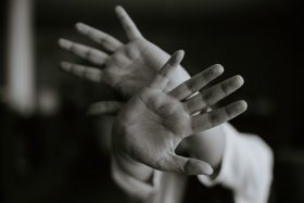 A grayscale photo of a person stretching their hands out in front of them, as if to shield themselves from a threat. Photo by M.T ElGassier on Unsplash.
