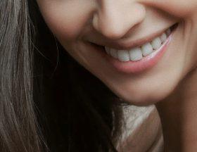 A close-up of a smiling woman. Photo by Alexander Krivistskiy on Unsplash.