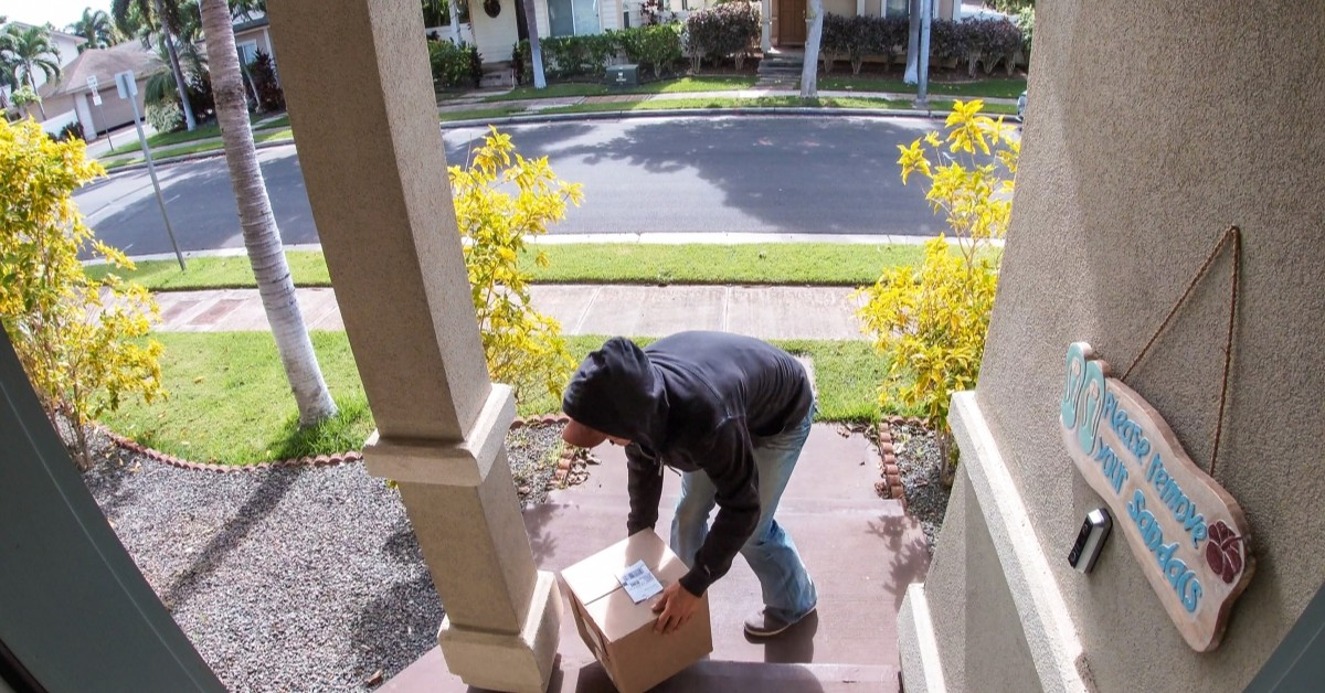 Man stealing a package off of a porch.