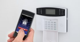 Homeowner arming a security system.