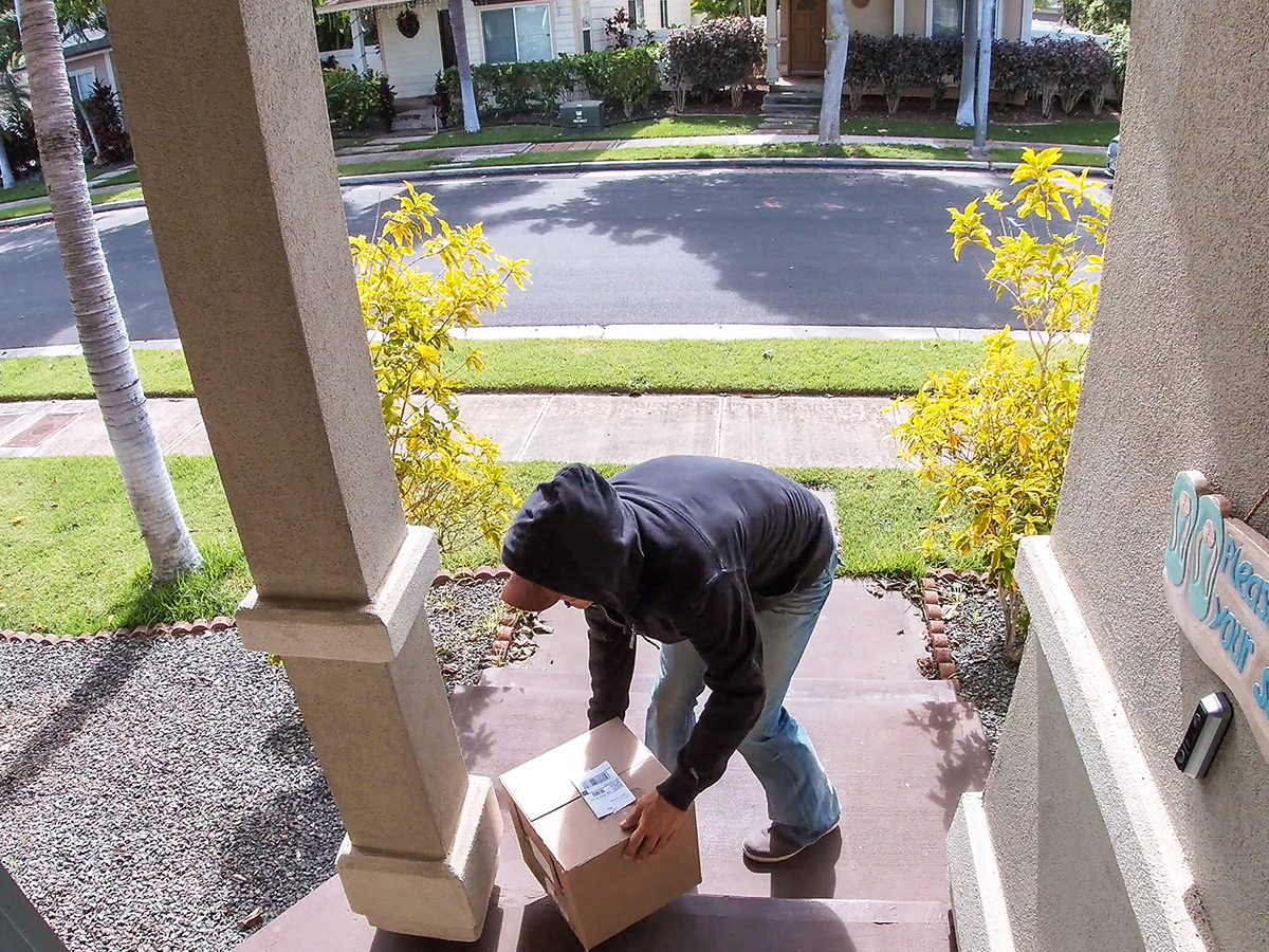 Camera view of a package being delivered or taken from a front door step.