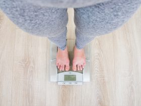An image of a person standing on a scale measuring their weight.