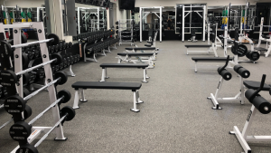 Dumbbells and benches in strength training area of the Fitness 19 gym