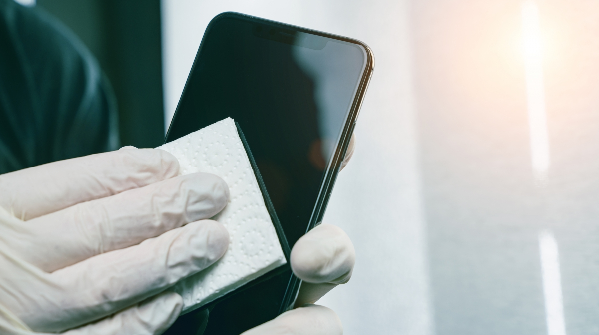 Someone wearing gloves and cleaning a phone screen.