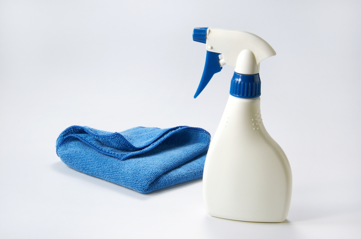 Bottle of a cleaning product with a rag.