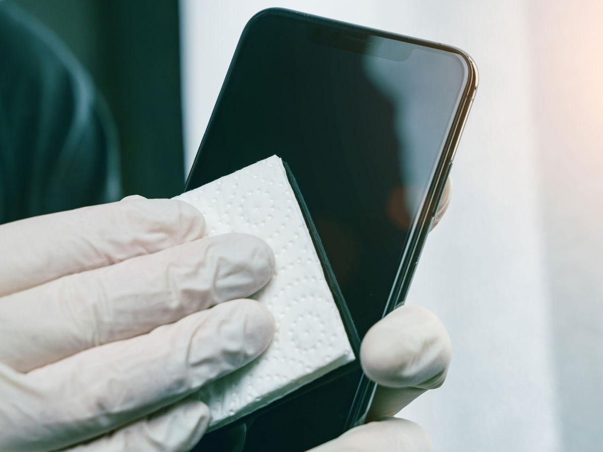 Image of someone wiping a cell phone screen