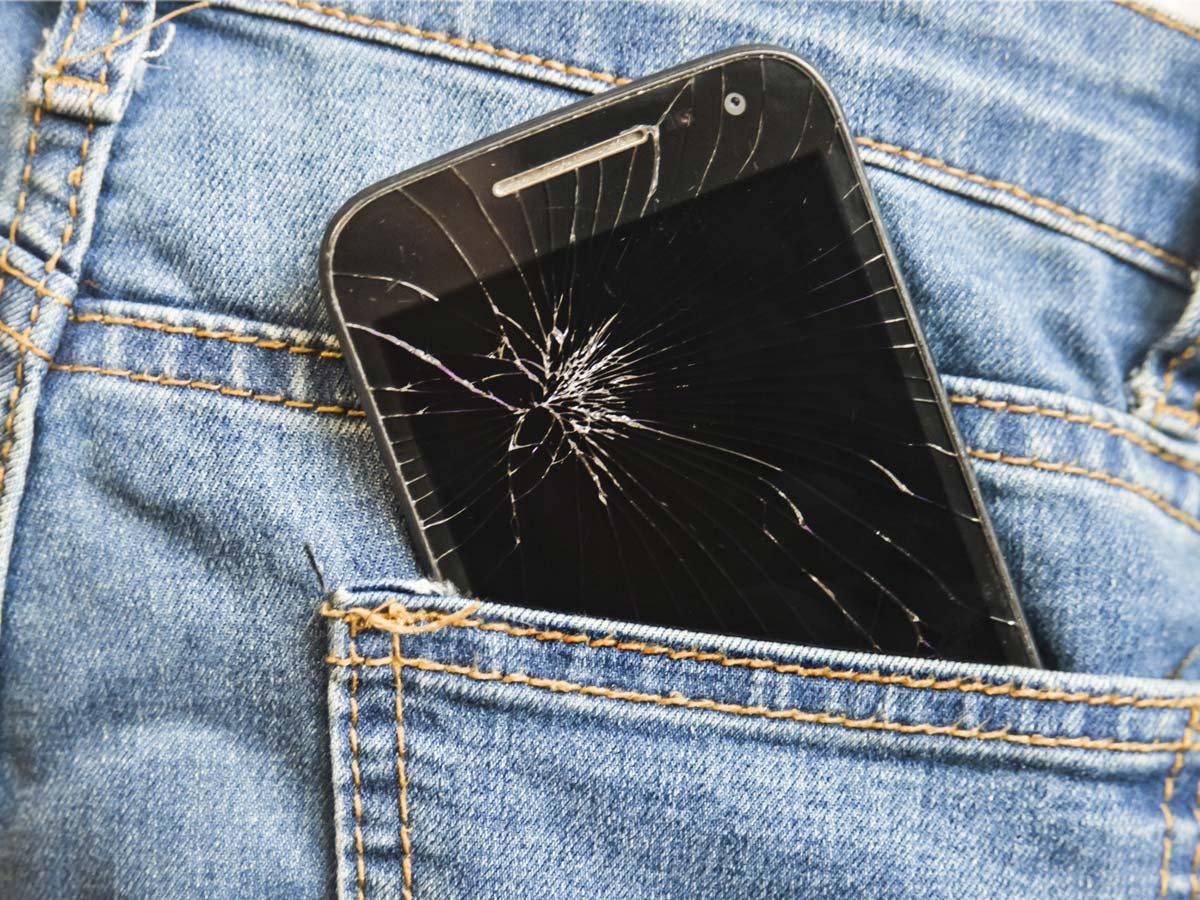 Image of a damaged cell phone in someone's back pocket