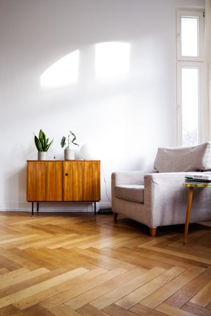 Living room with solid hardwood floors, grey couch, and a wooden end table. Photo by Beazy on Unsplash.