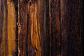 A close up photo of warm hued hardwood planks. Photo by Joshua Gresham on Unsplash.