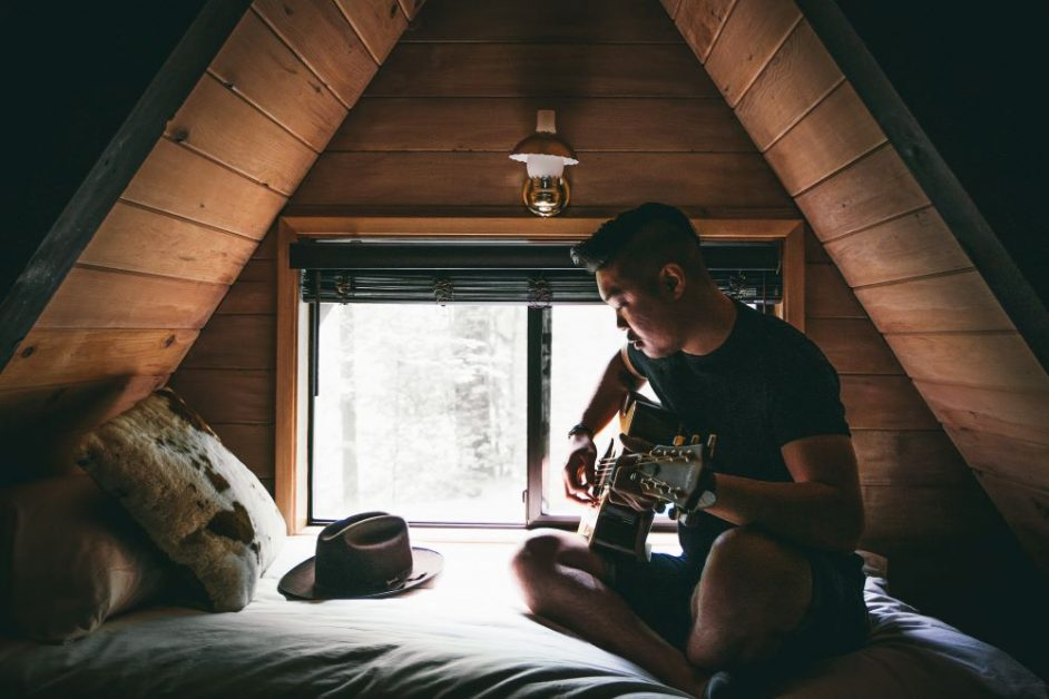 A man in a black t-shirt sits on a bed playing guitar. Photo by Andrew Ly on Unsplash.