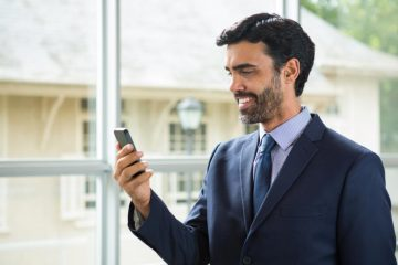 A businessman standing in front of a window using a mobile phone.