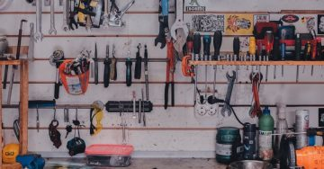 A collection of construction tools and hardware hangs on the wall of a garage.