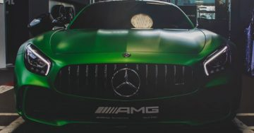 A medium shot of a green sports car in a garage.