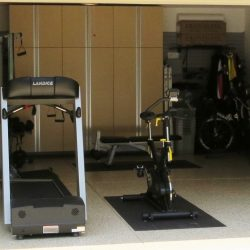 Garage turned into fitness center with epoxy floor coating and storage cabinets