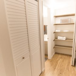 Hallway into a bathroom with closet and open shelving - Gateway Place Apartments