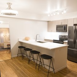 An open-concept kitchen with wood floors and modern look - Gateway Place Apartments