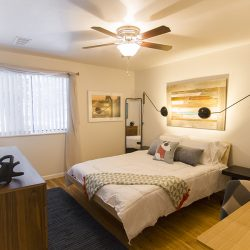 A large apartment bedroom with wood floors and ceiling fan - Gateway Place Apartments
