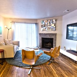 An apartment living room with fireplace, wood floors, and large window - Gateway Place Apartments