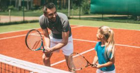 Image of father and daughter in tennis ready stances