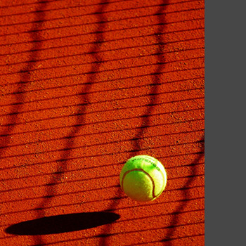 Close up of tennis ball about to contact red asphalt surface