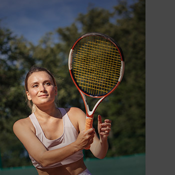 Image of woman grinning after successful tennis shot