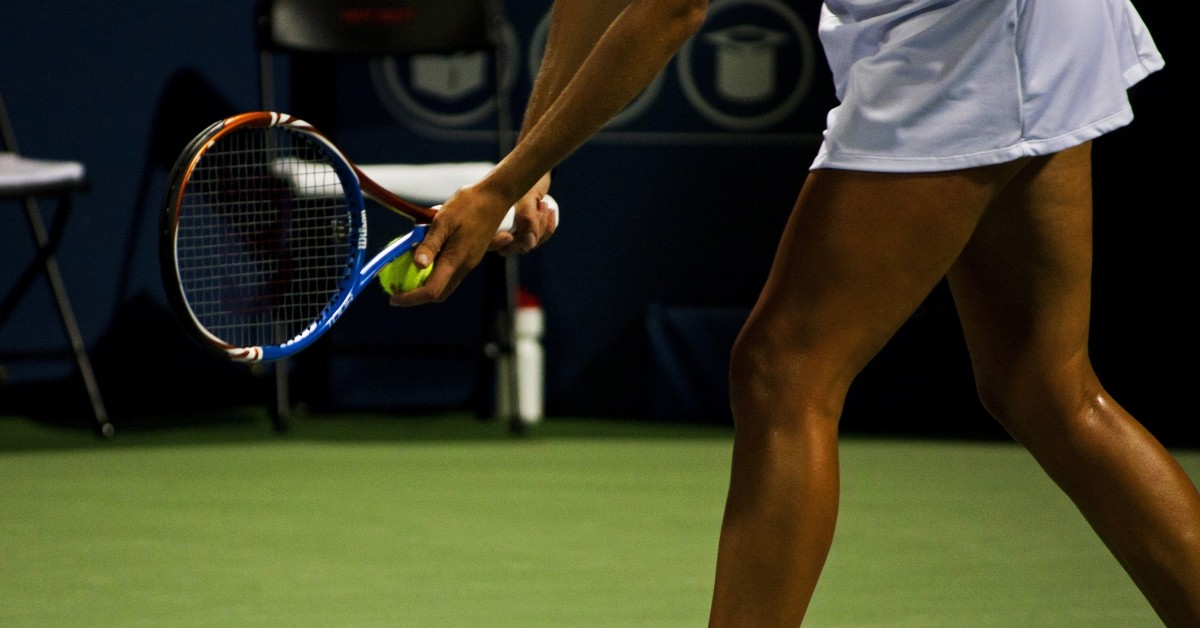 Image of woman's lower section getting ready to serve a tennis ball