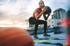 Woman squatting with medicine ball