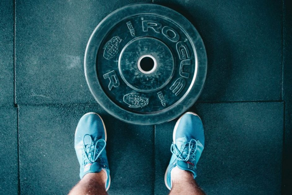 A birds-eye shot of a man wearing blue tennis shoes stands in front of a weightlifting plate. Photo by Victor Freitas for Unsplash.