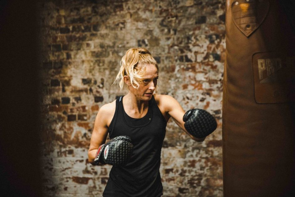 A woman in a black tank top and gloves boxes with a heavy exercise bag. Photo by Virgyl Sowah on Unsplash.