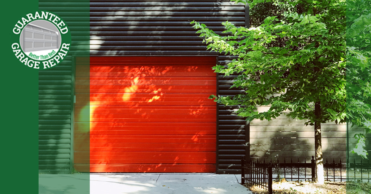 A edgy orange garage door in a black painted house.
