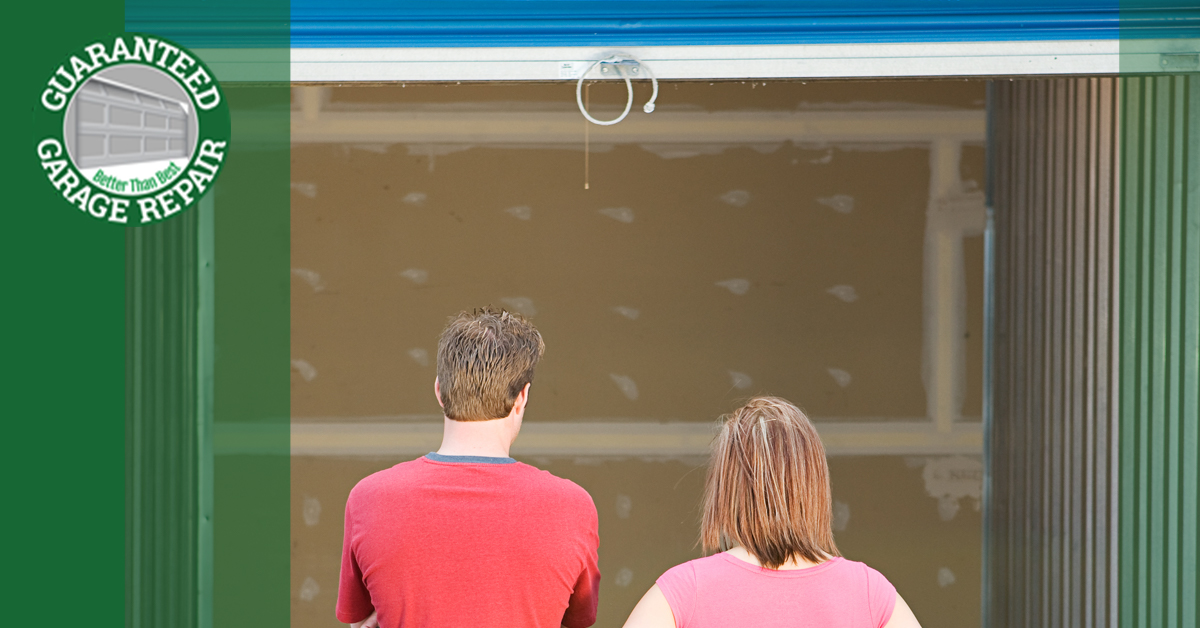 A young couple stare at an open garage.