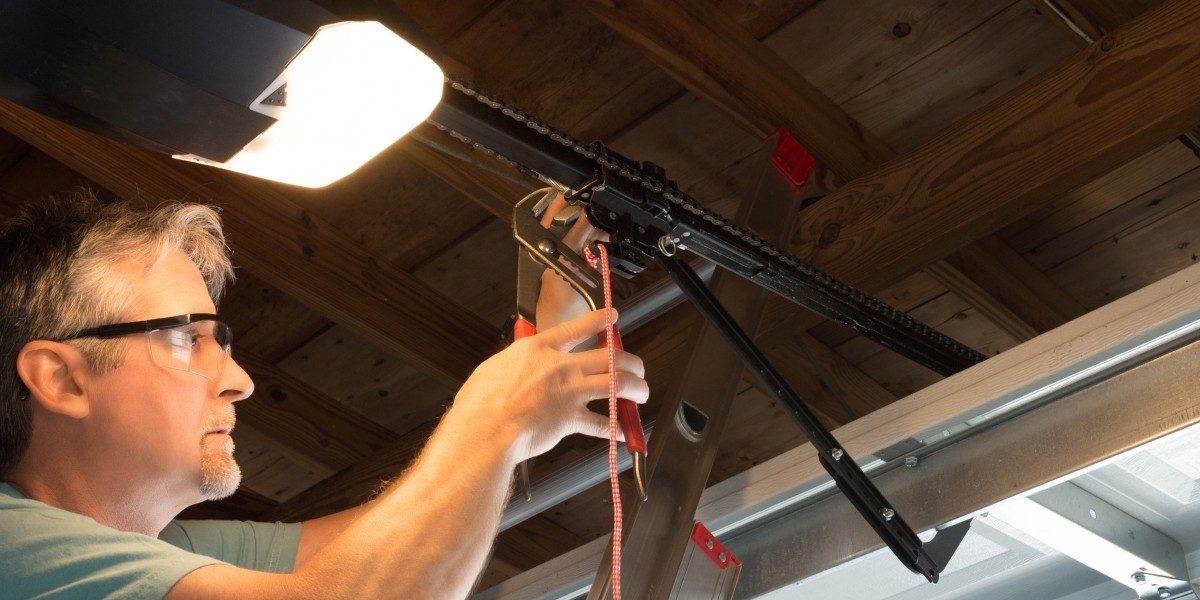 A man repairing the chain on a garage door opener.
