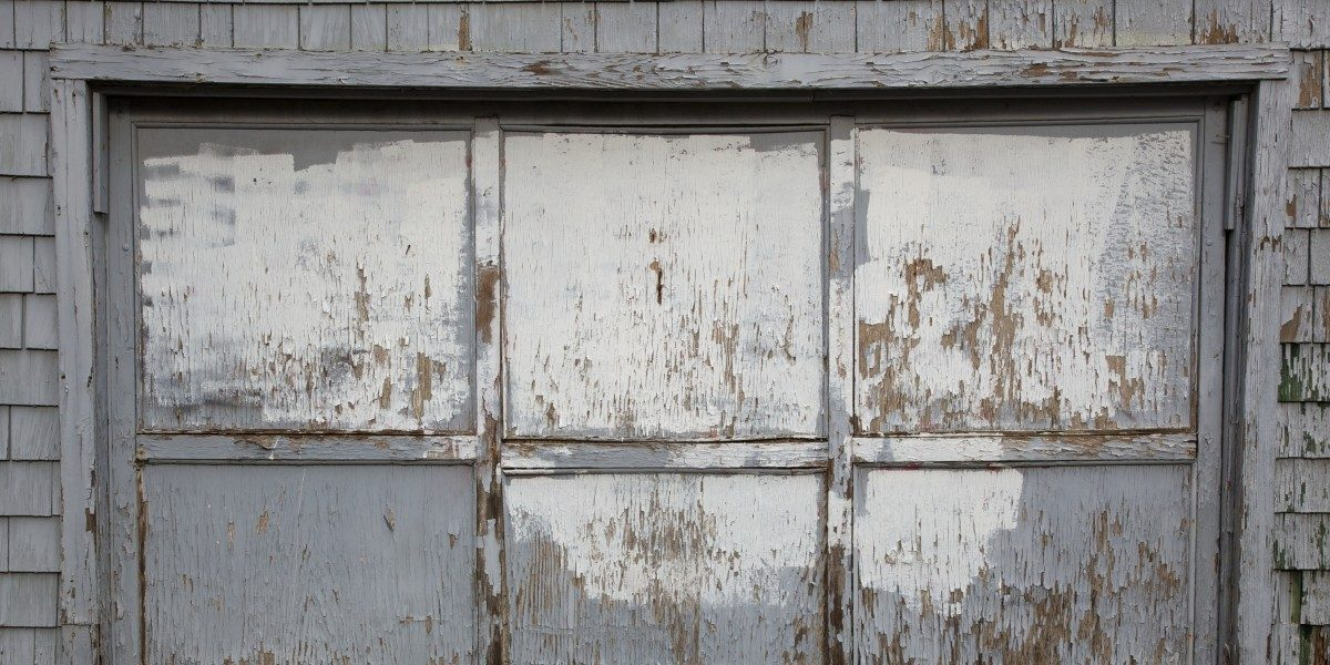 A decaying garage door with chipping white paint.