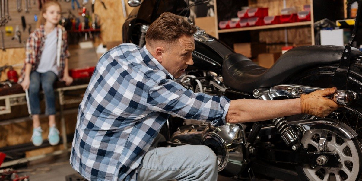A man repairing a motorbike.