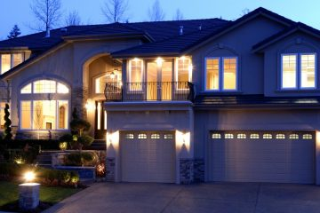 A house all lit up, with even the three car garage showing light through the windows.