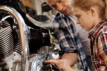 An image of a girl and a man working on a motorcycle.
