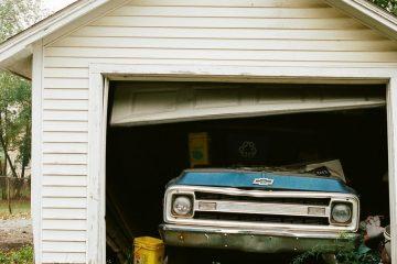 An image of an old blue truck in a a broken down garage.