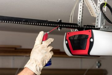 An image of a man using WD-40 on a garage door chain.