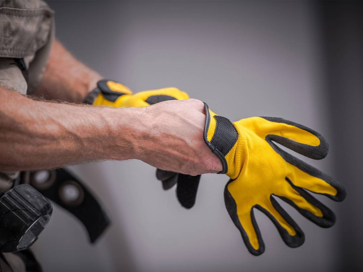 Image of a plumber putting on gloves.