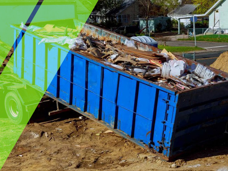 Truck dropping off a 40-yard blue dumpster in a dirt area.