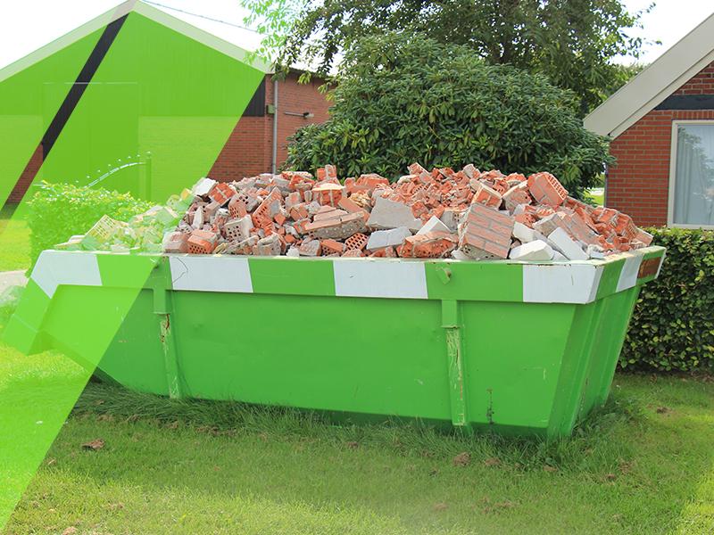 Green dumpster full of bricks sitting outside a home.
