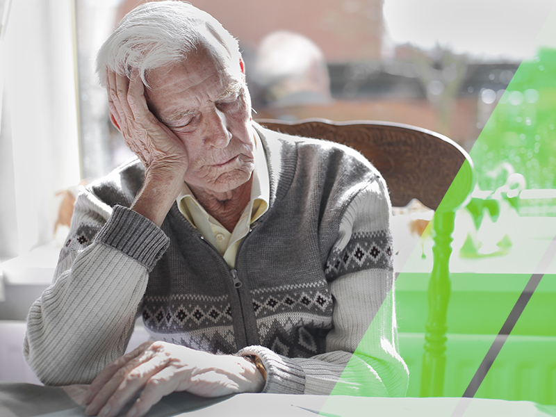 Elderly man sitting at a table with his head in his hand, sleeping.