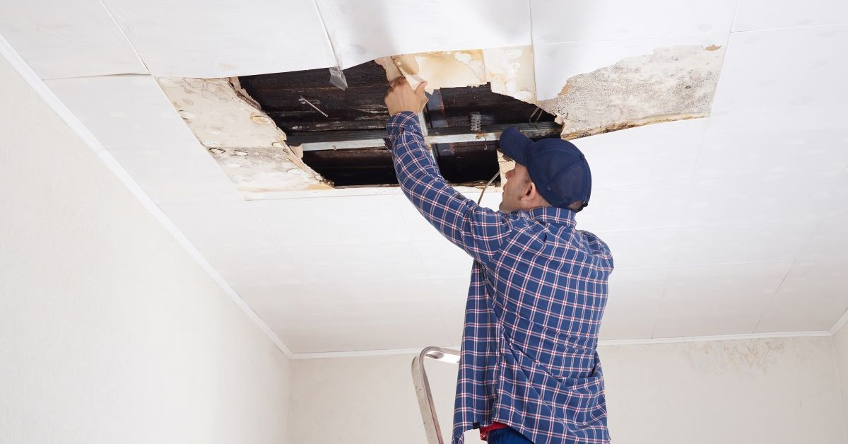 man fixing leaky roof