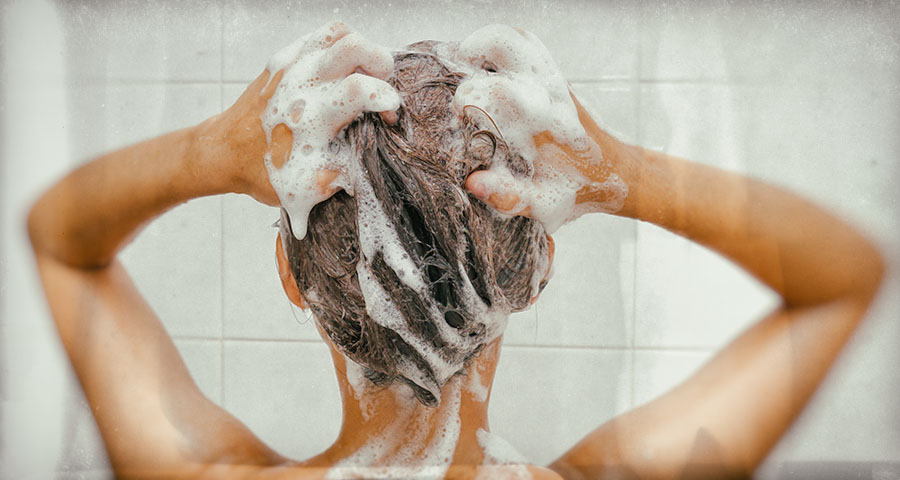 Woman scrubs head with lice shampoo in the shower.