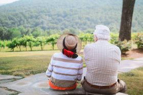 An older man and woman sit on a picnic blanket and look out over a rolling green landscape.