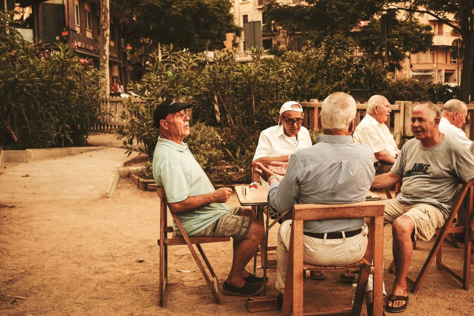 A group of senior citizen men sitting around a table outside. Photo by Cristina Gottardi on Unsplash.