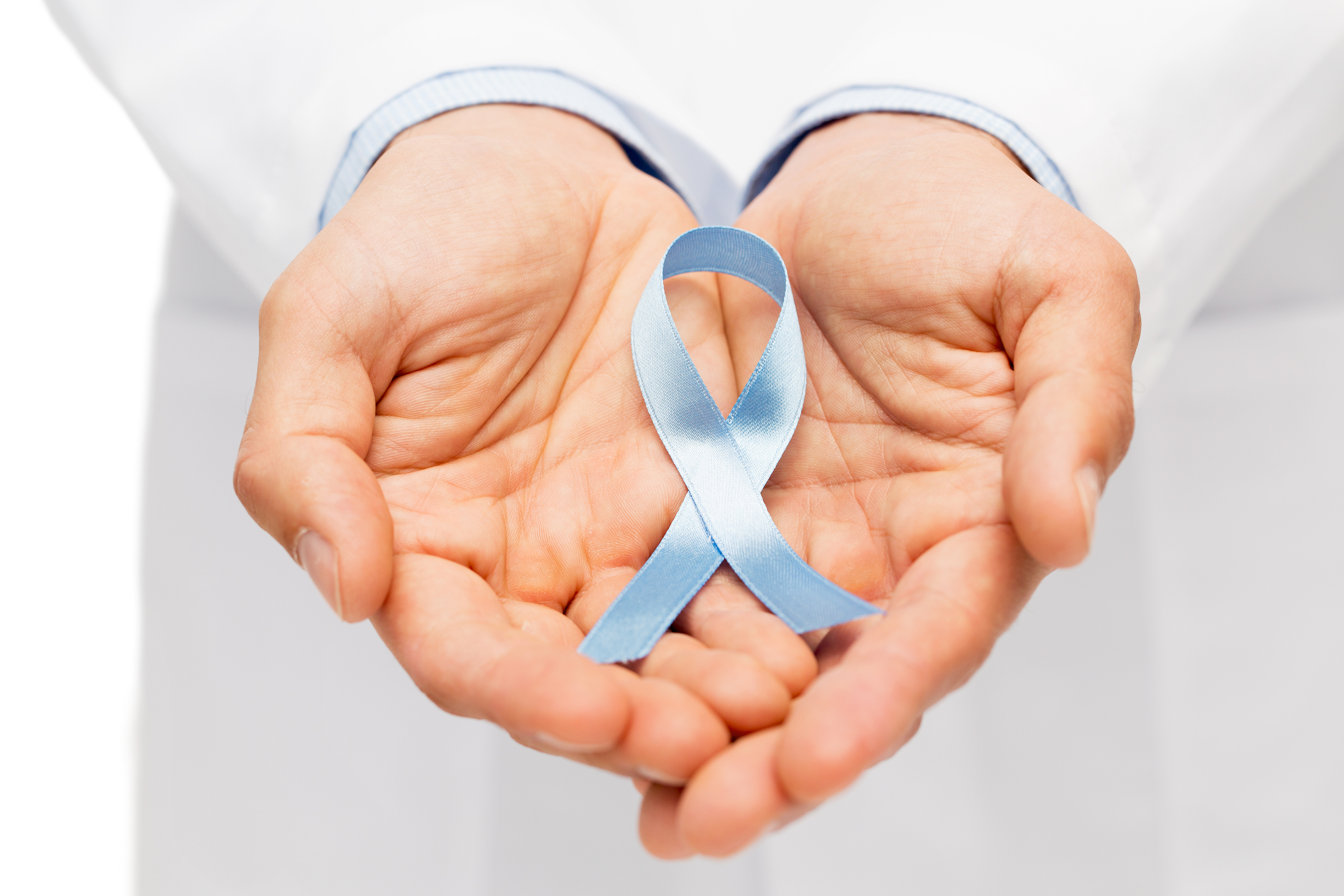 healthcare, profession, people and medicine concept - close up of male doctor hands holding sky blue prostate cancer awareness ribbon